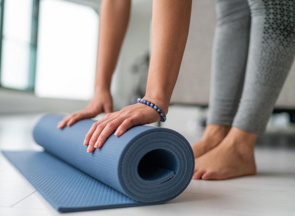 girl unrolling a yoga mat